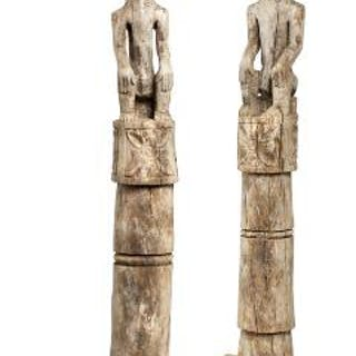 Two weathered wooden poles carved with ancestor figures
