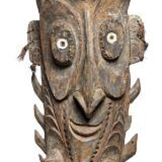 Figure of carved patinated wood with mask adorned with shells