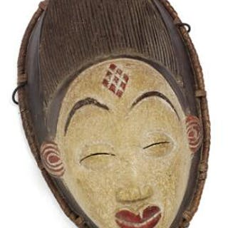 Mask of carved patinated wood decorated with black and red pigment and kaolin