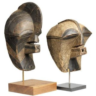 Two masks of carved patinated wood decorated with red