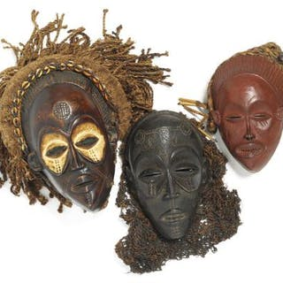 Three masks of carved patinated wood with traces of red and white pigment