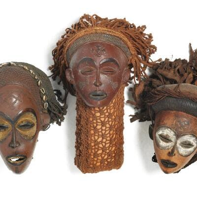 Three masks of carved patinated wood with traces of red and black pigment