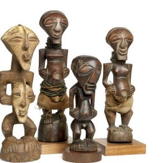 Four fetish figures of carved patinated wood clad with cloth