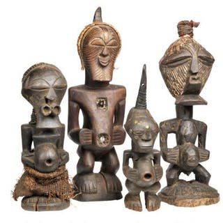 Four fetish figures of carved patinated wood mounted with horn