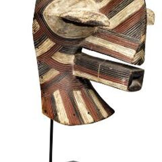 Mask of carved patinated wood decorated with red