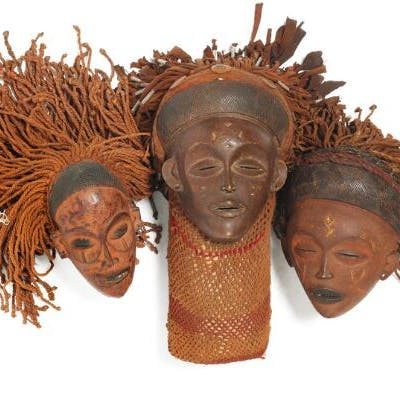 Three masks of carved patinated wood mounted with...