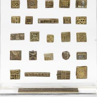 A collection of gold weights mounted on a board of plexiglass. Ashanti, Ghana.