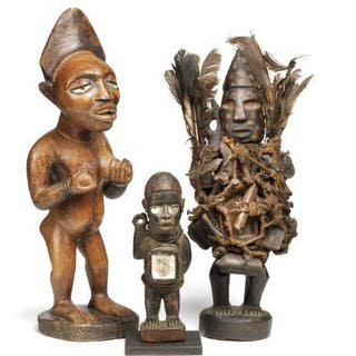 Three fetish figures of carved patinated wood clad with feathers