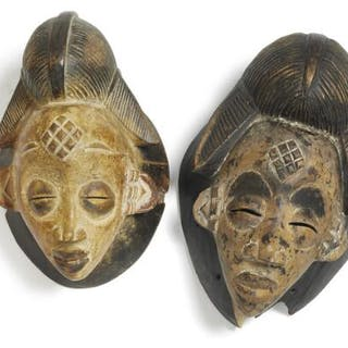Two masks of carved patinated wood decorated with kaolin