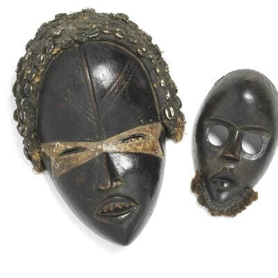 Two masks of carved patinated wood mounted with seashells