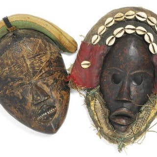 Two masks of carved patinated wood mounted with cloth and shells