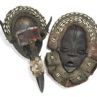 Two masks of carved patinated wood mounted with cloth and kaori shells