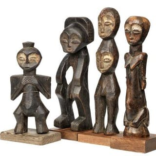 A collection of four ancestor figures of carved patinated...