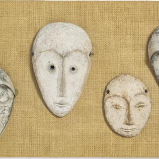 Four small masks of carved patinated wood decorated with kaolin