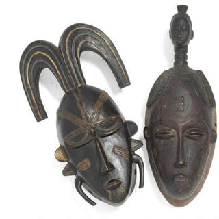 Two masks of carved patinated wood. Guro and Senofu style. H. 34 and 39 cm. (2)