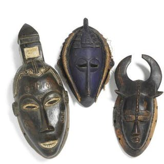 Three masks of carved patinated wood with traces of blue and white pigment