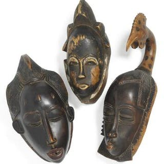 Three masks of carved patinated wood with traces of kaolin