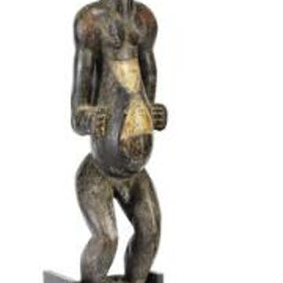 Large ancestor figure of carved patinated wood mounted with feathers