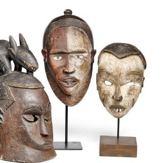 Two helmet masks and two masks of carved patinated wood with traces of red