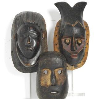 Three masks of carved patinated wood with traces of red