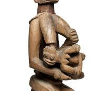 Fertility figure of carved patinated wood holding child