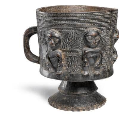 Vessel of carved black patinated wood with handle
