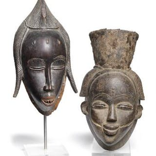 Two dancing masks of carved patinated wood