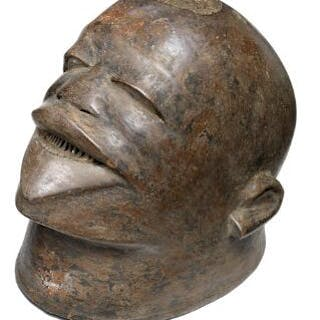 Helmet mask of carved patinated wood mounted with hair. Makonde style.