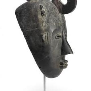 Dancing mask of carved black patinated wood