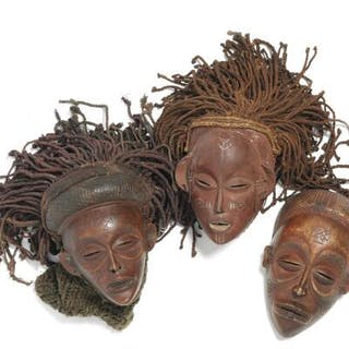 Three masks of carved patinated wood mounted with cloth and raffia