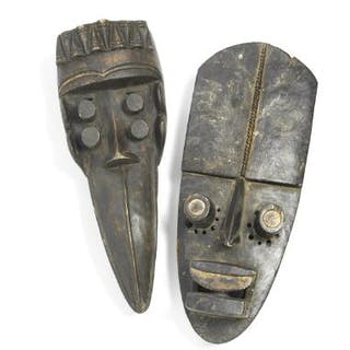 Two masks of carved patinated wood with traces of white kaolin