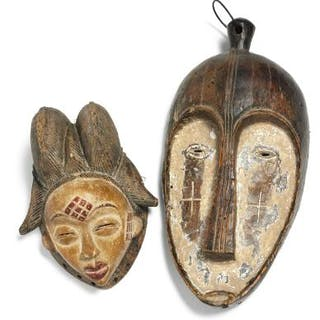 Two masks of carved patinated wood decorated with red and white pigment