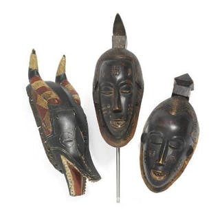Three masks of carved patinated wood with traces red