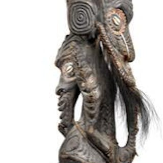 Ancestor figure of carved patinated wood mounted with teeth and feathers