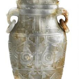 A Chinese covered vase of greenish jade carved in relief...