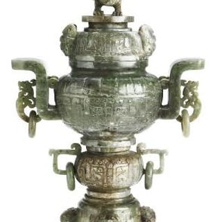 A Chinese covered vase of greenish jade carved with four ring handles