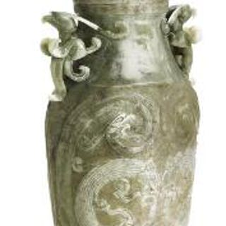 A Chinese covered vase of greenish jade carved in light...
