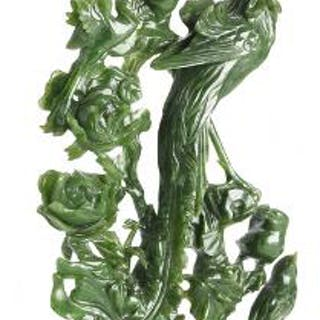A Chinese figure of green jade carved in the shape of birds and flowers