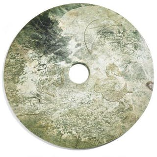 A Chinese disc (bi) of green jade carved in light relief with merfolk and moon