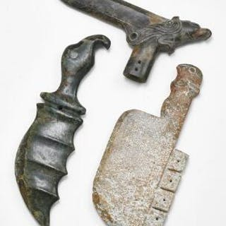 Three Chinese weapons of green and brownish jade in the shape of a dagger