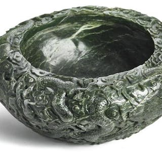 A large Chinese basin of green jade richly carved with...