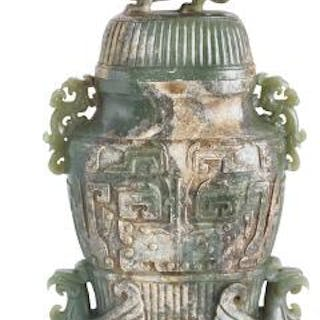 A Chinese covered vase of green jade carved in light relief with stylised