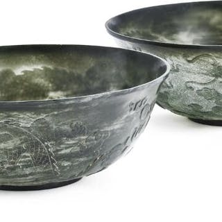 A pair of Chinese bowls of green jade carved with dragons...