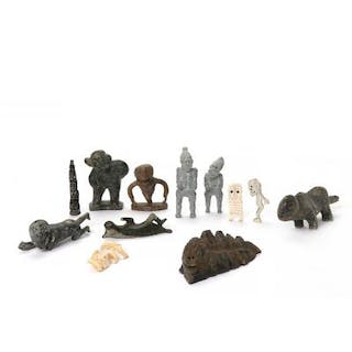 A collection of Greenlandic carved soapstone figures and carved bone tupilaks