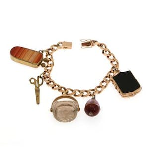A 14k gold charm bracelet set with five different metal charms. L.