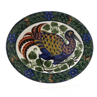 An oval faience dish decorated in colours with a pheasant