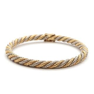 A twisted 18k gold and white gold bangle. L. app. 21 cm. Weight app. 29.5 g.