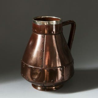 A Doulton pottery ewer simulating beaten copper