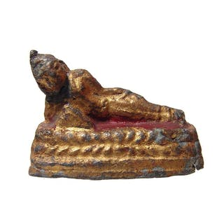 A little gilded figure of Buddha reclined on a bed