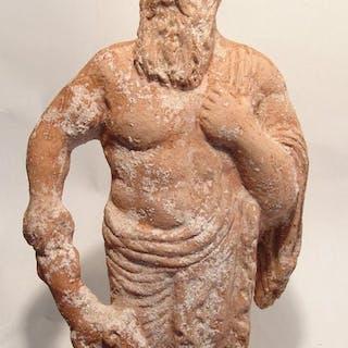 A large Greek terracotta figure of a bearded deity